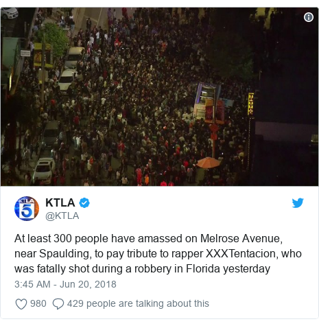 Twitter post by @KTLA: At least 300 people have amassed on Melrose Avenue, near Spaulding, to pay tribute to rapper XXXTentacion, who was fatally shot during a robbery in Florida yesterday