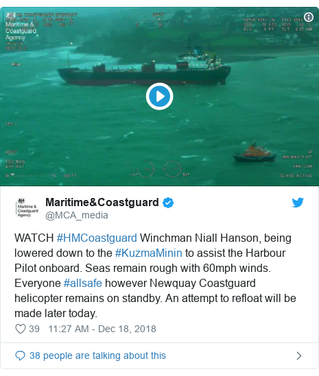 Twitter post by @MCA_media: WATCH #HMCoastguard Winchman Niall Hanson, being lowered down to the #KuzmaMinin to assist the Harbour Pilot onboard. Seas remain rough with 60mph winds. Everyone #allsafe however Newquay Coastguard helicopter remains on standby. An attempt to refloat will be made later today.