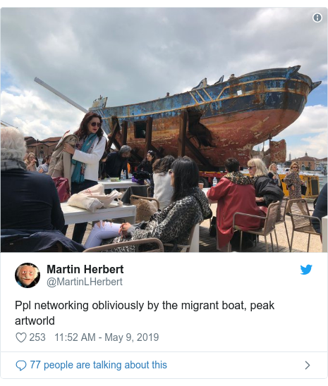 Twitter post by @MartinLHerbert: Ppl networking obliviously by the migrant boat, peak artworld