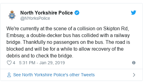 Twitter post by @NYorksPolice: We're currently at the scene of a collision on Skipton Rd, Embsay, a double-decker bus has collided with a railway bridge. Thankfully no passengers on the bus. The road is blocked and will be for a while to allow recovery of the debris and to check the bridge.