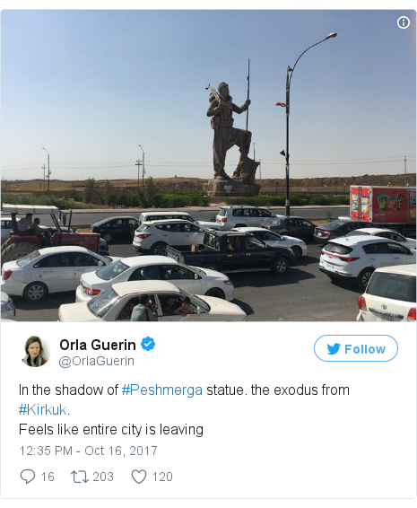 Twitter post by @OrlaGuerin: In the shadow of #Peshmerga statue. the exodus from #Kirkuk.Feels like entire city is leaving