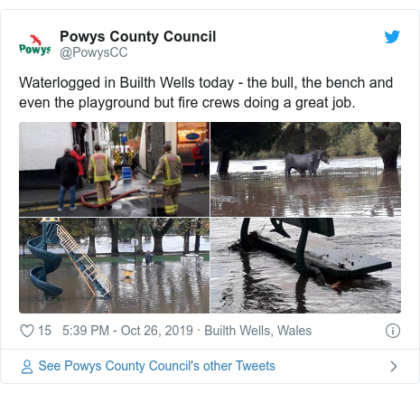 Twitter post by @PowysCC: Waterlogged in Builth Wells today - the bull, the bench and even the playground but fire crews doing a great job.