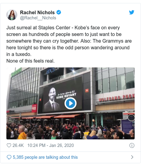 Twitter post by @Rachel__Nichols: Just surreal at Staples Center - Kobe's face on every screen as hundreds of people seem to just want to be somewhere they can cry together. Also  The Grammys are here tonight so there is the odd person wandering around in a tuxedo.None of this feels real.
