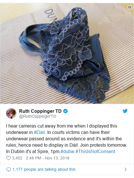 Twitter post by @RuthCoppingerTD: I hear cameras cut away from me when I displayed this underwear in #Dáil. In courts victims can have their underwear passed around as evidence and it's within the rules, hence need to display in Dáil. Join protests tomorrow. In Dublin it's at Spire, 1pm.#dubw #ThisIsNotConsent
