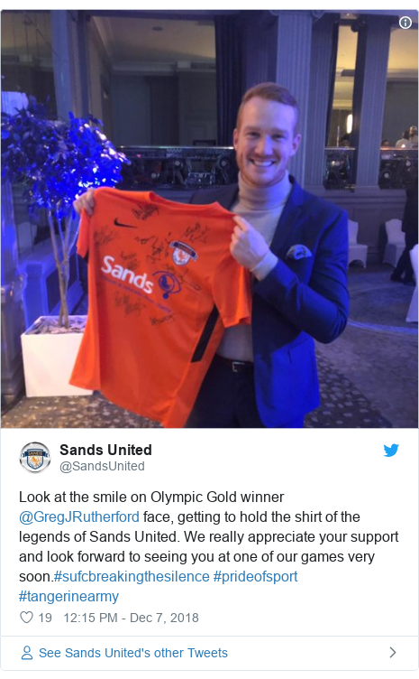 Twitter post by @SandsUnited: Look at the smile on Olympic Gold winner @GregJRutherford face, getting to hold the shirt of the legends of Sands United. We really appreciate your support and look forward to seeing you at one of our games very soon.#sufcbreakingthesilence #prideofsport #tangerinearmy