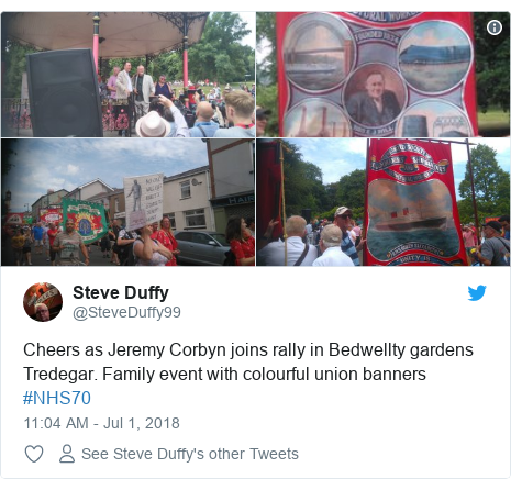 Twitter post by @SteveDuffy99: Cheers as Jeremy Corbyn joins rally in Bedwellty gardens Tredegar. Family event with colourful union banners #NHS70