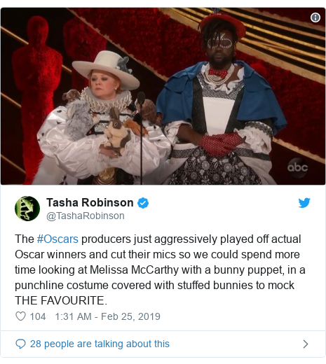 Twitter post by @TashaRobinson: The #Oscars producers just aggressively played off actual Oscar winners and cut their mics so we could spend more time looking at Melissa McCarthy with a bunny puppet, in a punchline costume covered with stuffed bunnies to mock THE FAVOURITE.