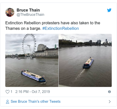 Twitter post by @TheBruceThain: Extinction Rebellion protesters have also taken to the Thames on a barge. #ExtinctionRebellion