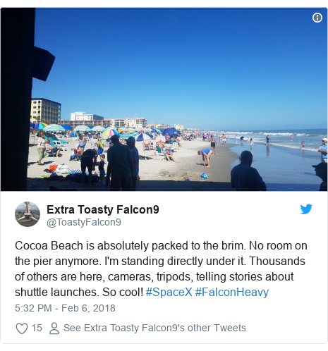 Twitter post by @ToastyFalcon9: Cocoa Beach is absolutely packed to the brim. No room on the pier anymore. I'm standing directly under it. Thousands of others are here, cameras, tripods, telling stories about shuttle launches. So cool! #SpaceX #FalconHeavy