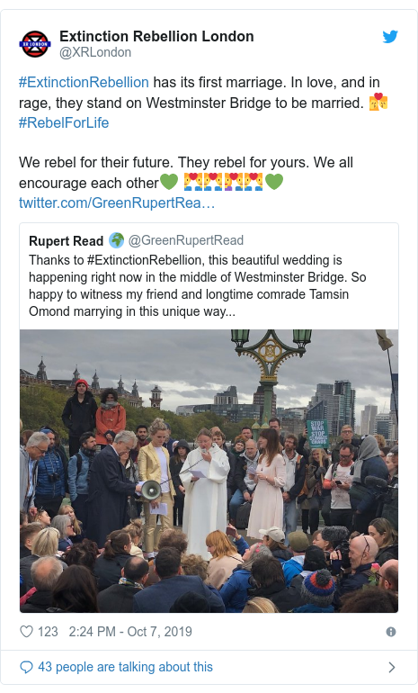 Twitter post by @XRLondon: #ExtinctionRebellion has its first marriage. In love, and in rage, they stand on Westminster Bridge to be married. 👩❤️💋👨#RebelForLifeWe rebel for their future. They rebel for yours. We all encourage each other💚 👨❤️👨👨❤️👨👩❤️👨👨❤️👨💚