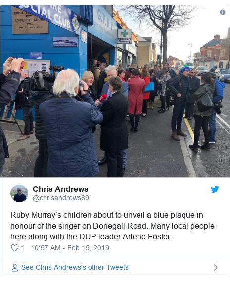 Twitter post by @chrisandrews89: Ruby Murray's children about to unveil a blue plaque in honour of the singer on Donegall Road. Many local people here along with the DUP leader Arlene Foster.