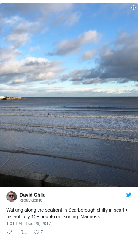 Twitter post by @davidchild: Walking along the seafront in Scarborough chilly in scarf + hat yet fully 15+ people out surfing. Madness.