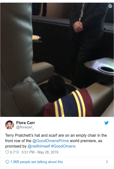 Twitter post by @floracarr_: Terry Pratchett's hat and scarf are on an empty chair in the front row of the @GoodOmensPrime world premiere, as promised by @neilhimself #GoodOmens