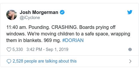 Twitter post by @iCyclone: 11 40 am. Pounding. CRASHING. Boards prying off windows. We're moving children to a safe space, wrapping them in blankets. 969 mg. #DORIAN