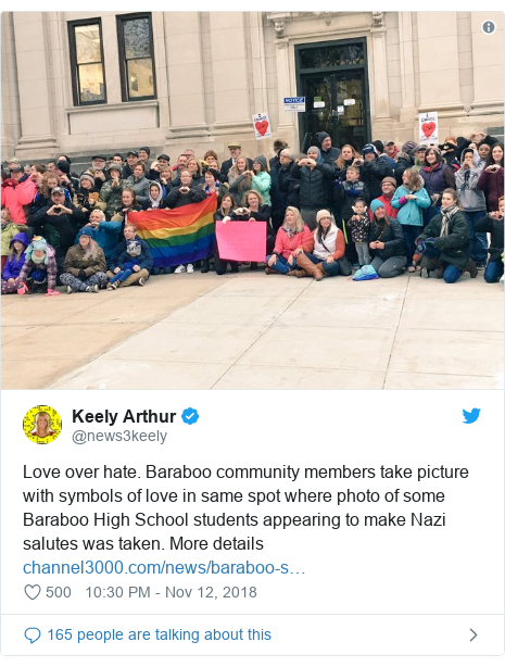 Twitter post by @news3keely: Love over hate. Baraboo community members take picture with symbols of love in same spot where photo of some Baraboo High School students appearing to make Nazi salutes was taken. More details