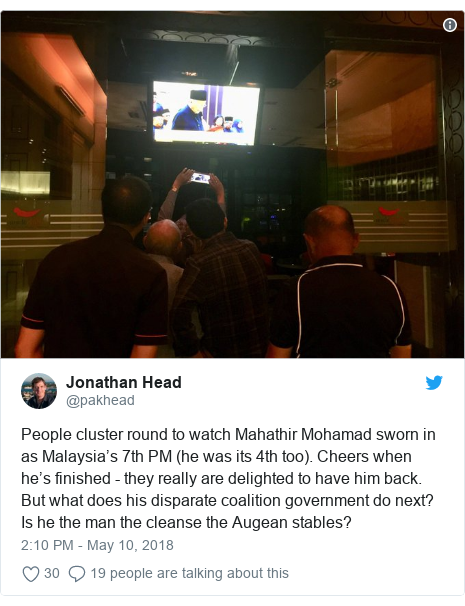 Twitter post by @pakhead: People cluster round to watch Mahathir Mohamad sworn in as Malaysia's 7th PM (he was its 4th too). Cheers when he's finished - they really are delighted to have him back. But what does his disparate coalition government do next? Is he the man the cleanse the Augean stables?