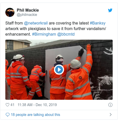 Twitter post by @philmackie: Staff from @networkrail are covering the latest #Banksy artwork with plexiglass to save it from further vandalism/ enhancement. #Birmingham @bbcmtd