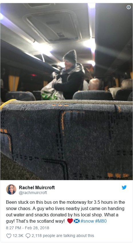 Twitter post by @rachmuircroft: Been stuck on this bus on the motorway for 3.5 hours in the snow chaos. A guy who lives nearby just came on handing out water and snacks donated by his local shop. What a guy! That's the scotland way!  ❤️🏴 #snow #M80