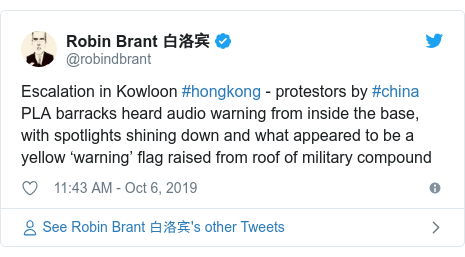Twitter post by @robindbrant: Escalation in Kowloon #hongkong - protestors by #china PLA barracks heard audio warning from inside the base, with spotlights shining down and what appeared to be a yellow 'warning' flag raised from roof of military compound