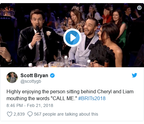 "Twitter post by @scottygb: Highly enjoying the person sitting behind Cheryl and Liam mouthing the words ""CALL ME."" #BRITs2018"