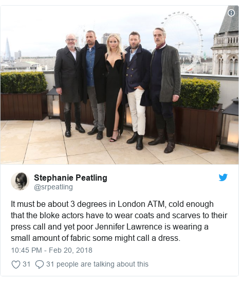 Twitter post by @srpeatling: It must be about 3 degrees in London ATM, cold enough that the bloke actors have to wear coats and scarves to their press call and yet poor Jennifer Lawrence is wearing a small amount of fabric some might call a dress.