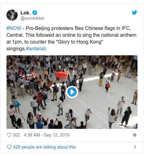 """Twitter post by @sumlokkei: #NOW - Pro-Beijing protesters flies Chinese flags in IFC, Central. This followed an online to sing the national anthem at 1pm, to counter the """"Glory to Hong Kong"""" singings.#antielab"""