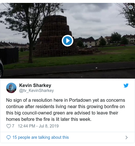Twitter post by @tv_KevinSharkey: No sign of a resolution here in Portadown yet as concerns continue after residents living near this growing bonfire on this big council-owned green are advised to leave their homes before the fire is lit later this week.