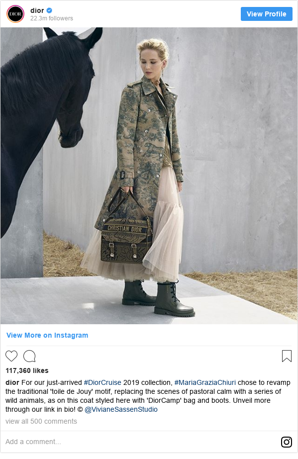Instagram post by dior: For our just-arrived #DiorCruise 2019 collection, #MariaGraziaChiuri chose to revamp the traditional 'toile de Jouy' motif, replacing the scenes of pastoral calm with a series of wild animals, as on this coat styled here with 'DiorCamp' bag and boots. Unveil more through our link in bio! © @VivianeSassenStudio