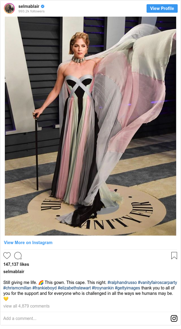 Instagram post by selmablair: Still giving me life. 🌈 This gown. This cape. This night. #ralphandrusso #vanityfairoscarparty #chrismcmillan #frankieboyd #elizabethstewart #troynankin #gettyimages thank you to all of you for the support and for everyone who is challenged in all the ways we humans may be. 💛