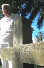 Swiss surgeon, Hans-Peter Muller, stands beside Albert Schweitzer's grave