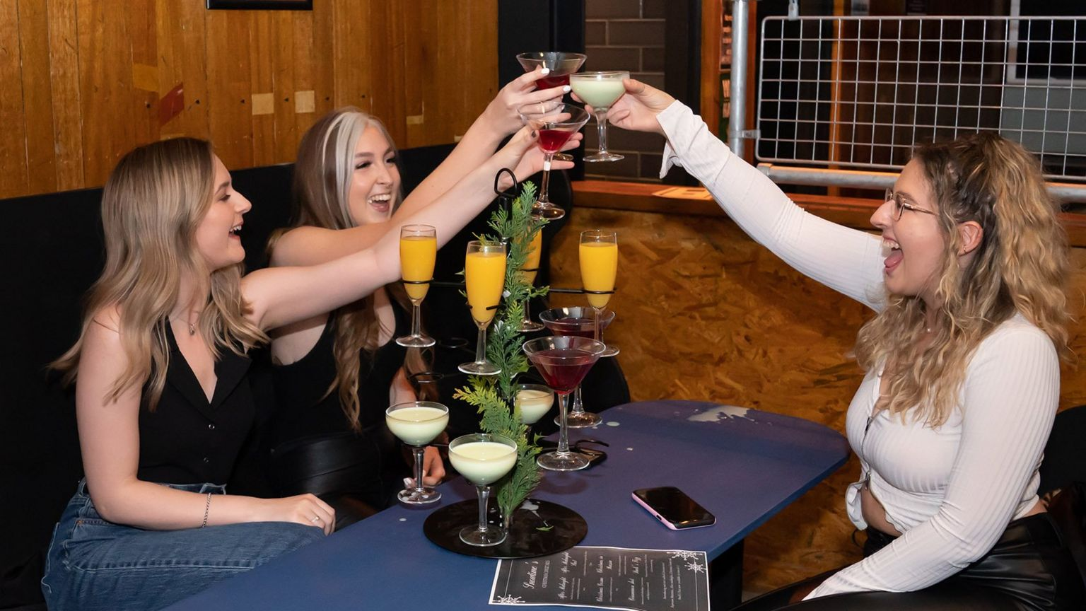 Rosie Delaney, Isobel Loan and Rebecca Mitchell get their first drink at 00:11 at the Showtime Bar in Huddersfield, West Yorkshire