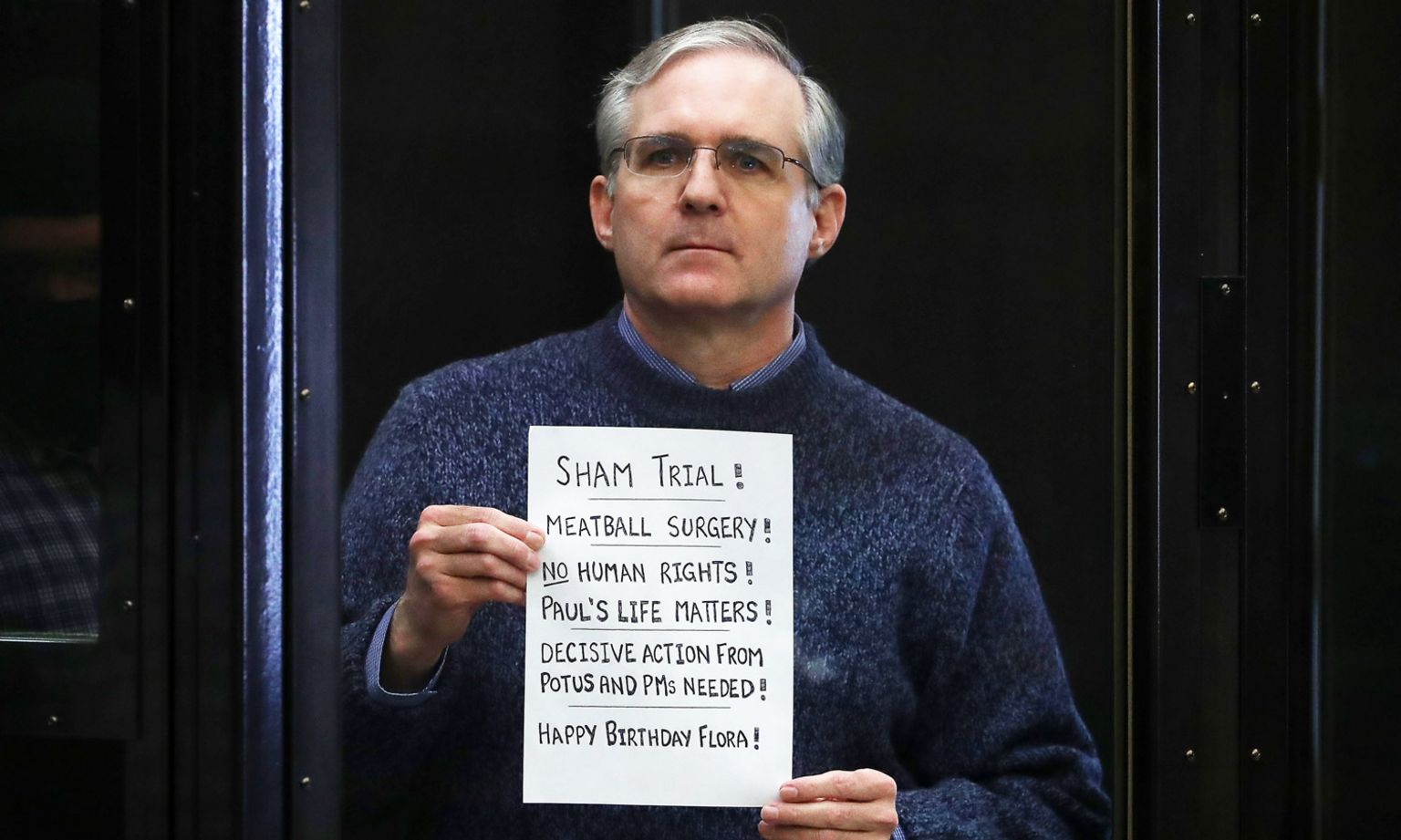 """Paul Whelan holds up a sign at the end of his trial - """"Sham trial! Meatball surgery! No human rights! Paul's life matters! Decisive action from potus and PMs needed! Happy Birthday Flora!"""""""