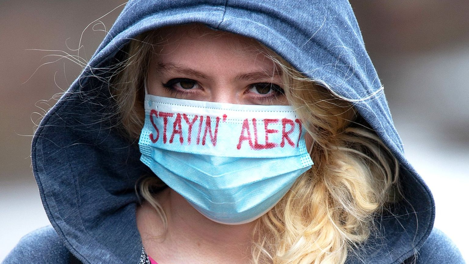 """Young woman wearing a face mask with the words """"stayin' alert"""" on it"""