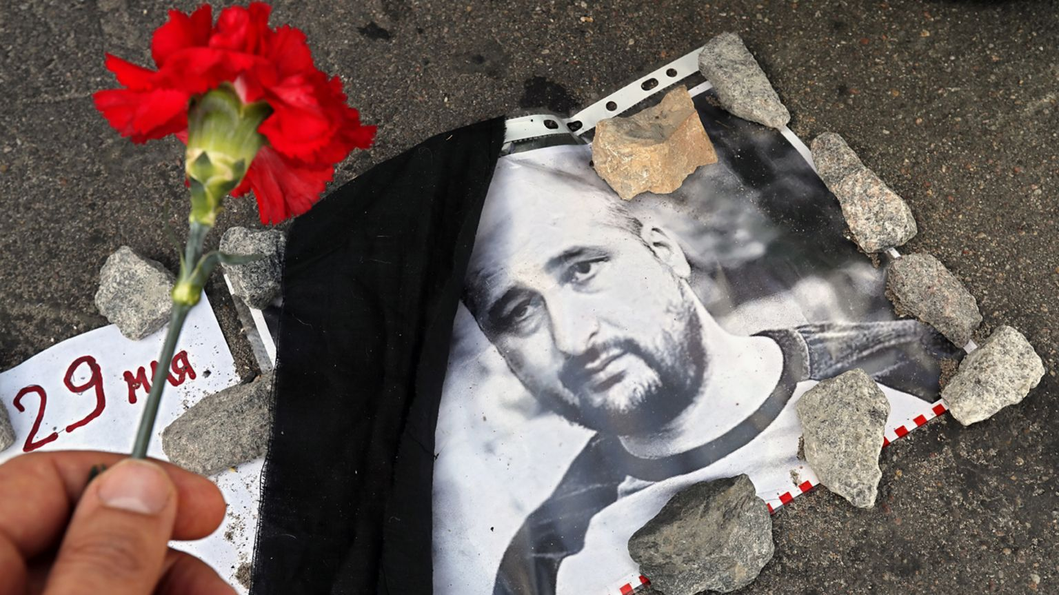 A flower is laid next to a photo of Arkady Babchenko