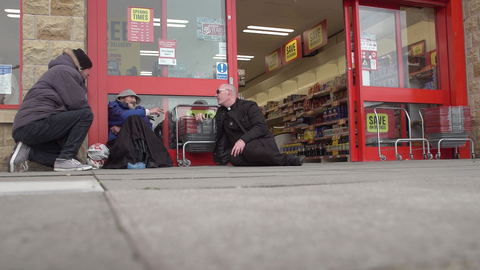 Pastor Mick Fleming talks to a man on the ground outside a shop