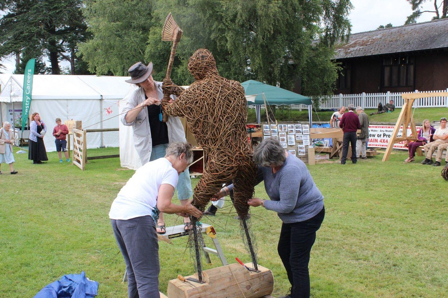 Mae o'n ffodus na fedr o symud ei freichiau! // This 'Wicker Man' is given a leg up by volunteers