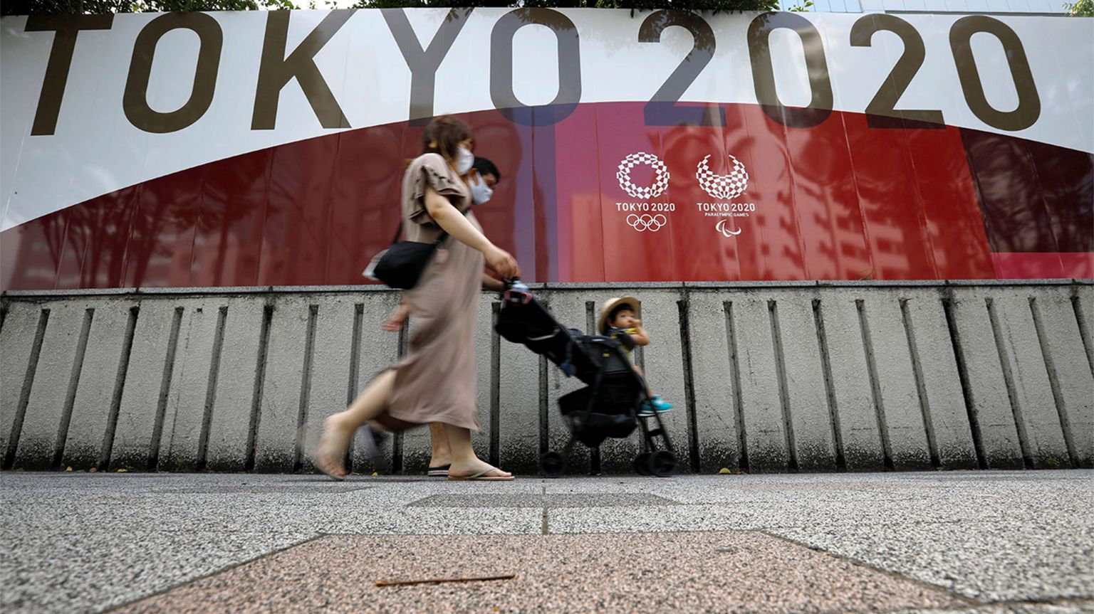 A family walks by a billboard for the Tokyo Olympics in Tokyo