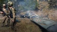 Pakistani soldiers near what appears to be aircraft wreckage