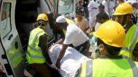 Saudi emergency personnel and Hajj pilgrims load a wounded person into an ambulance