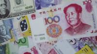 Selection of notes of different currencies with a Chinese note on top