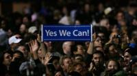An Obama supporter holds up a sign which reads 'Yes we can' during his victory speech in Chicago