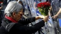 A demonstrator holds flowers before a police barricade during a commemoration for the victims of Saturday's bomb blasts in the Turkish capital, in Ankara, Turkey, 11 October 2015