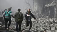 Syrian man carries an infant injured in government bombing in the besieged Eastern Ghouta region of Damascus