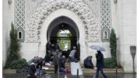 Muslims pray by the entrance of the Great Mosque of Paris
