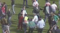 Sarah Hicks being carried from the pitch by spectators on a makeshift stretcher