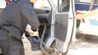 Police officer pulling out a snake from a van in China