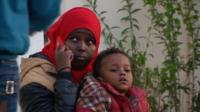 Migrant survivor on phone