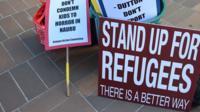 Placards on ground outside Australia High Court following Nauru asylum ruling