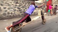 Tumaini riding his chukudu, which looks like a stretched wooden bicycle