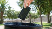 Someone throwing a smartphone into a bin